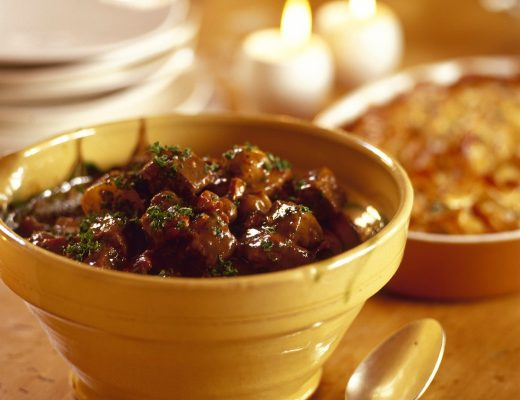Ceramic bowl of beef bourguignon with parsley on a wooden table set with candles.
